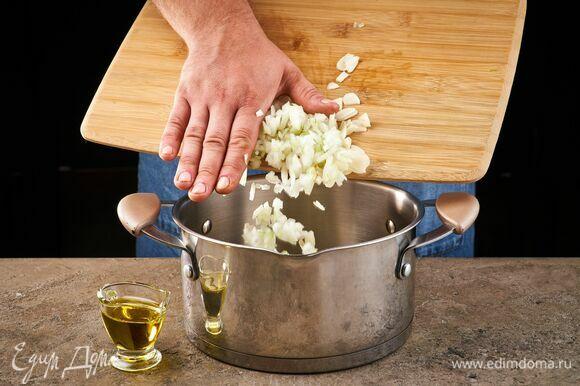 Влейте в кастрюлю оливковое масло и пожарьте лук и чеснок.