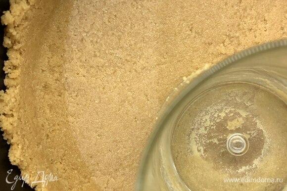 Выложить половину массы в форму, плотно утрамбовать стаканом с плоским дном, затем выложить вторую часть и сделать бортики. Форму с песочной основой поставить в холодильник.