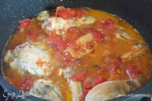 Вернуть к колбасе кусочки курицы, влить вино, добавить помидоры, чеснок, соль по вкусу и бульон. Поставить на средний огонь, довести до кипения и уменьшить огонь до минимума. Тушить 40 минут.