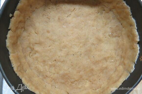 Дно формы диаметром 20 см застелить бумагой для выпечки, выложить тесто и руками распределить его по форме, сформировав бортики. Форму с тестом убрать в холодильник на 30 минут.