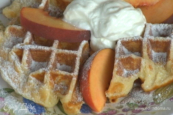 Готовые вафли подавать с персиками, присыпав сахарной пудрой и украсив йогуртом.