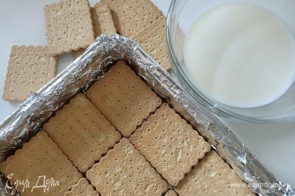 Форму застелить пищевой пленкой или фольгой. Выложить слой печенья, предварительно окунув его в молоко.