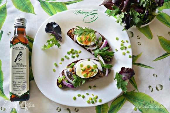 На каждый кусок хлеба положить по 4 кусочка сельди, 1–2 кружочка нарезанного яйца, красный и зеленый лук. Полить соусом. Украсить салатным миксом и тут же подавать! Приятного вам аппетита!