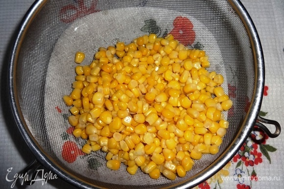 Консервированную кукурузу выложить на дуршлаг, чтобы стекла жидкость.