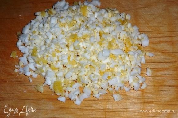 Яйца отварить вкрутую. Охладить в холодной воде, почистить и нарезать мелкими кубиками.