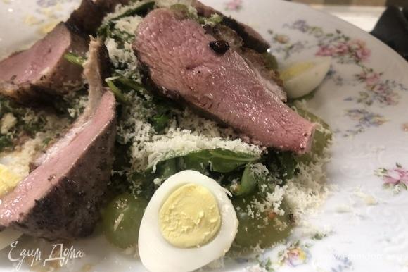 Собираем салат: первым отправляем руколу, добавляем нарезанные вдоль перепелиные яйца, натираем на мелкой терке пармезан и сверху выкладываем нарезанную слайсами утиную грудку. Приятного аппетита.