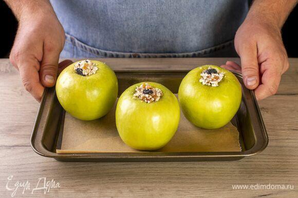 Нафаршируйте яблоки. Выложите яблоки в форму и запекайте при 140℃ около 15 минут.