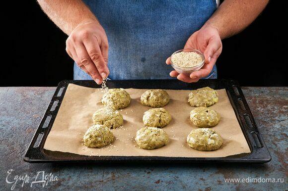 Сформируйте шарики и выложите на противень, застеленный пергаментной бумагой. Сверху шарики посыпьте семечками кунжута. Выпекайте в духовке, разогретой до 180°C, около 30 минут.