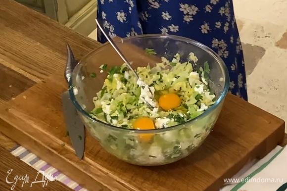 Выложить капусту в глубокую миску, добавить творог, 2 яйца и измельченную зелень, все посолить и перемешать.