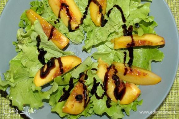 Нектарин раскладываем поверх листьев салата и поливаем бальзамическим кремом.
