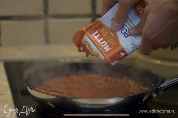 Добавить томаты в сковороду с обжаренными луком, чесноком и перцем. Тушить на медленном огне.
