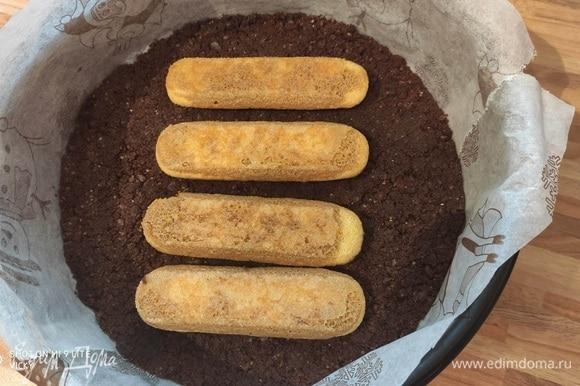 Достаньте форму с основой из духовки. Убавьте температуру в духовке до 170°C. Заварите крепкий кофе, остудите. Ненадолго окуните савоярди в кофе (печенье не должно пропитаться жидкостью полностью). Вплотную уложите печенье на основу торта.