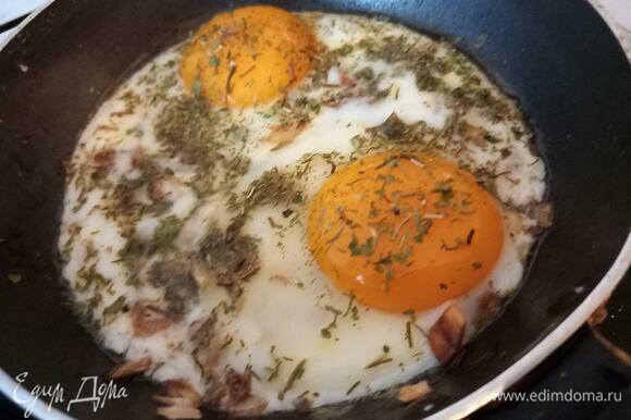 Через 2 минуты снять крышку и пожарить яичницу еще пару минут. При желании не схватившийся белок аккуратно можно распределить по площади другого белка.