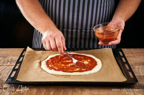 Раскатайте тесто в круглую форму, сформировав небольшие бортики, выложите на противень, застеленный пергаментом. Смажьте основу томатным соусом.