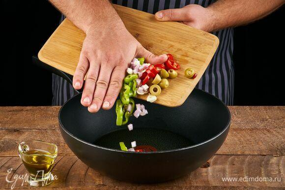 Разогрейте в сковороде 2 ст. л. оливкового масла. Выложите измельченный чеснок, перец чили, шалот и оливки, прогрейте, чтобы масло напиталось ароматами.