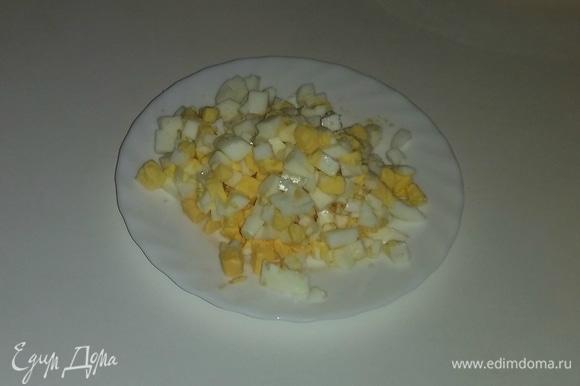 Куриные яйца сварить вкрутую, остудить и очистить от скорлупы. Затем нарезать.