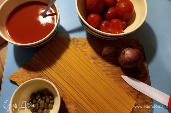 Подготовим ингредиенты. Томаты выловить из жидкости и сложить в отдельную пиалу. Лук и чеснок почистить.