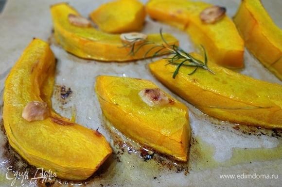 Тыкву нарезать на крупные куски, полить растительным маслом, добавить зубчик чеснока, веточку розмарина и запечь в духовке до золотистого цвета.