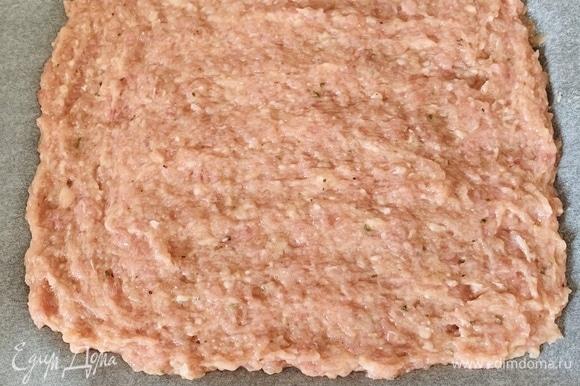 Фарш смешать с яйцом и специями до однородности. Выложить тонким слоем на противень, покрытый пергаментом. Отправить в духовку, разогретую до 190°C, на 10 минут.