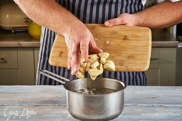 В кастрюле вскипятите воду, посолите и порциями отварите ньокки, следите за тем, чтобы они не слипались между собой. Из воды доставайте с помощью шумовки, когда ньокки всплывут. Затем переложите ньокки в сковороду к соусу, добавьте сливочное масло и прогрейте все на среднем огне.