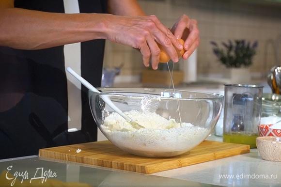 Приготовить тесто: кокосовую стружку и предварительно размягченное сливочное масло выложить в глубокую посуду и вымешать до однородной консистенции, добавить сахарную пудру, ванильный экстракт, желток, 2 яйца и вымешать тесто сначала лопаткой, затем руками.