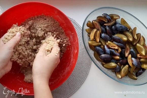 Мягкое сливочное масло соединить с сахаром, ванильным сахаром и мукой. Руками перетереть в крошку. Засыпать крошкой сливы и убрать в разогретую до 180°C духовку на 30–35 минут.