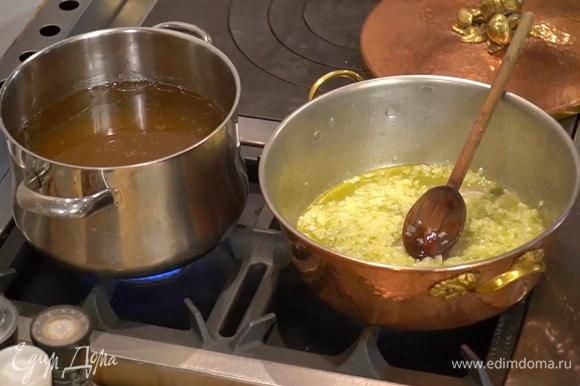 Разогреть в тяжелой, глубокой сковороде 1/2 ст. ложки сливочного и оливковое масло и слегка обжарить лук, затем добавить чеснок и на медленном огне готовить все до прозрачности.