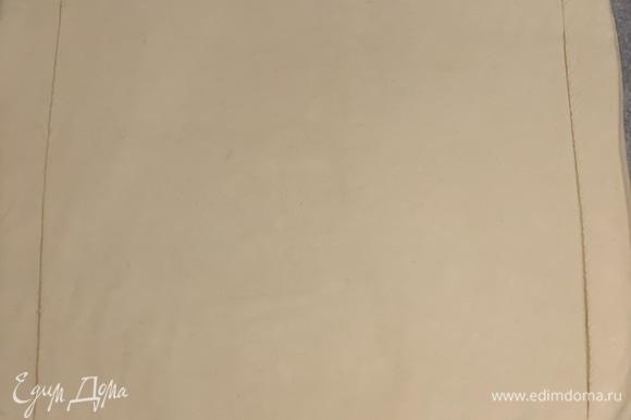 На пергаменте раскатываем тесто в прямоугольник и надрезаем, оставляя с каждой стороны по 1–1,5 см.