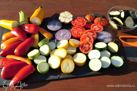 Пробежимся по огороду, соберем все нужные ингредиенты для приготовления блюда. Овощи промыть. Кабачки, баклажаны, лук, помидоры нарезать кольцами. Баклажаны 20 минут подержать в растворе соли, чтобы убрать горечь. Перцы очистить от семян и нарезать, чеснок разрезать поперек головки. Овощи сбрызнуть маслом.