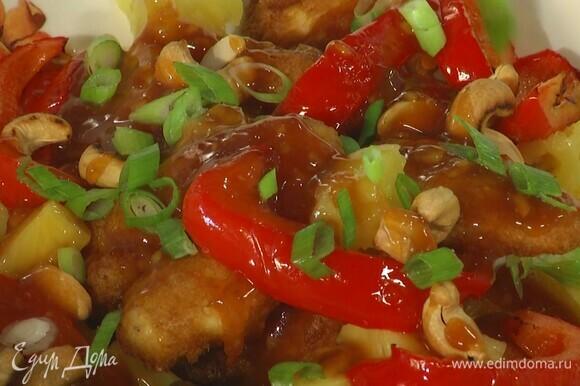 Выложить на тарелку обжаренную курицу, перец, ананасы и кешью, полить все соусом и посыпать зеленым луком.
