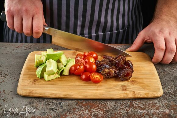 Из фиников удалите косточки и нарежьте плоды на две части. Томаты тоже разрежьте пополам. Авокадо очистите и нарежьте крупно.