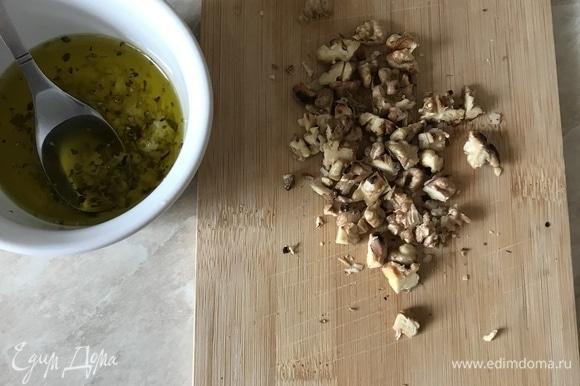 Пока жарятся сухарики, приготовим заправку. В пиале смешать оливковое масло, чеснок (лучше выдавить через пресс), орегано и хорошо перемешать. Орехи прокалить на сковороде, очистить от шелухи и порубить ножом.