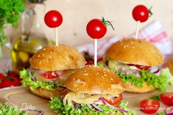 Формируем бургер: булочка, соус, салат, котлета, соус, лук, помидор, сыр, булочка. Здесь уже можно включить фантазию и собирать бургер в любой последовательности с любыми ингредиентами. Сыр я тонко режу, кладу на сухую сковороду и плавлю на ней, затем уже расплавленный сыр кладу на бургер.