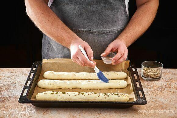 Смажьте заготовки водой и посыпьте смесью семян. Оставьте еще на 10 минут. Выпекайте багеты в течение 7 минут при 220°С, затем еще 25 минут при 180°С.