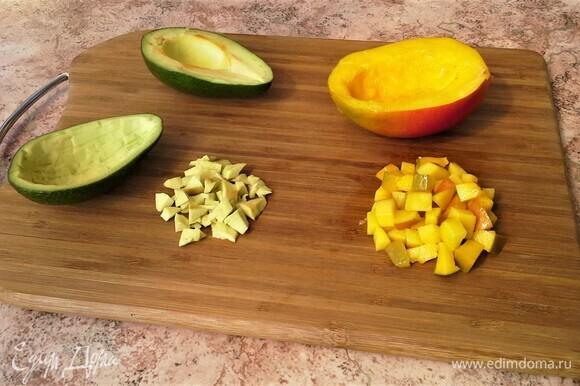 Авокадо разрежьте пополам, удалите косточки. Аккуратно извлеките мякоть из каждой половинки, и нарежьте мелкими кубиками, сбрызните соком лайма, кожуру не выбрасывайте. Кубиком нарежьте мякоть манго.