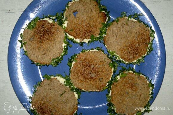 Боковую часть кусочков хлеба смазать майонезом. Обвалять в нарезанной зелени.