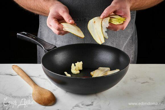 Очистите грушу от сердцевины и нарежьте тонкими слайсами. На сковороде разогрейте сливочное масло, выложите кусочки груши.