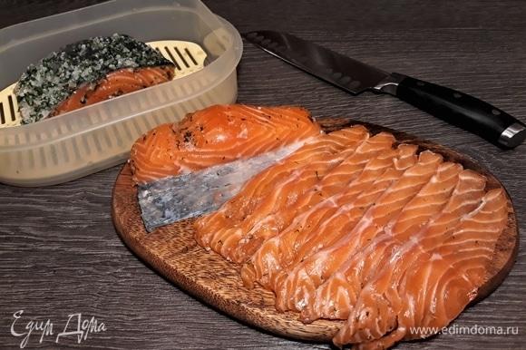 Достаем из холодильника. Тщательно очищаем ножом рыбу от соли, укропа и пряностей. Нарезаем тонкими ломтиками.