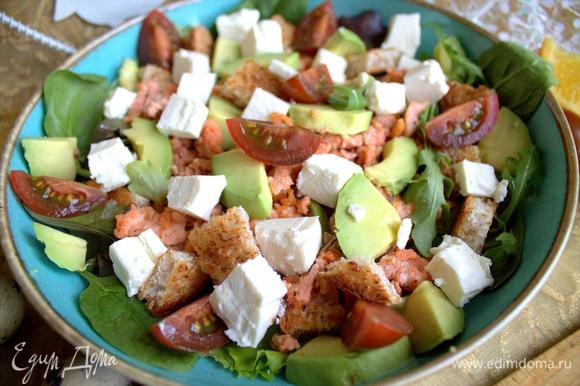 Рассыпать по салату фету, дольки томата и авокадо, оставшиеся сухарики также.