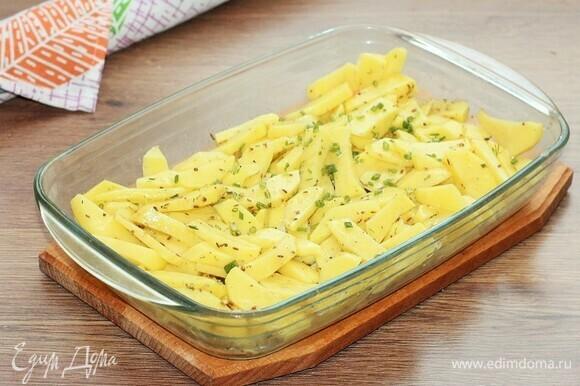 Очищенный и нарезанный брусочками картофель выкладываем в форму для запекания. Добавляем нарезанный полукольцами лук (0,5 шт.), порубленный укроп (0,5 пуч.) и чеснок (1 зуб.), 3 ст. л. подсолнечного масла и приправу для картофеля (1 ч. л.), солим и перчим. Перемешиваем картофель так, чтобы он был покрыт маслом.