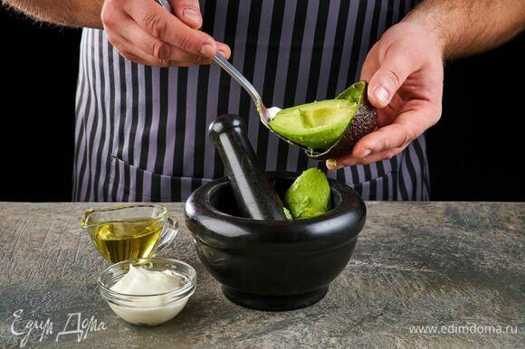 Авокадо очистите и тоже переложите в ступку. Добавьте сметану и оливковое масло.