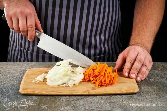 Нарежьте лук полукольцами, а морковь — тонкими брусочками.