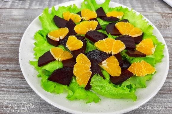 Выкладываем на салатные листья свеклу, мандарины, кусочки феты и посыпаем орехами. Я еще украсила руколой.