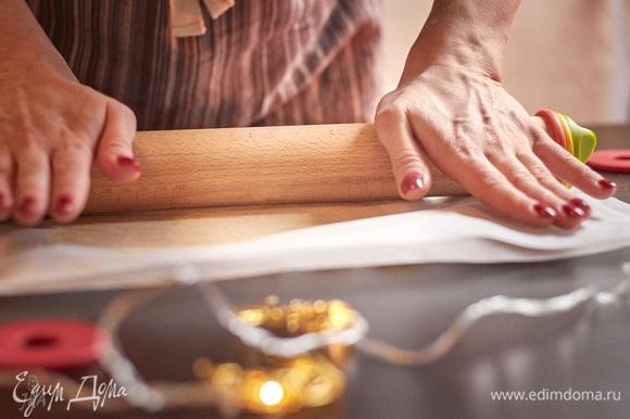 Охлажденное песочное тесто раскатать между двух листов пергамента до толщины 2 мм. Очень удобно делать это скалкой с кольцами, постепенно уменьшая их.