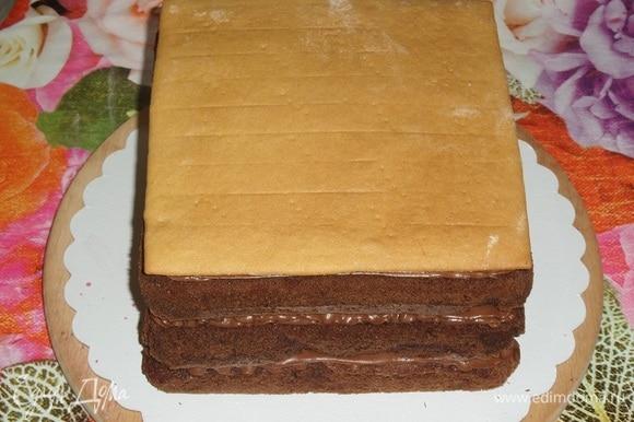 Поверх шоколадного крема укладываем медовый корж. Оборачиваем торт пленкой и кладем сверху небольшой груз, у меня это разделочная доска весом 400 г. Оставляем торт на 4–6 часов в холодильнике.