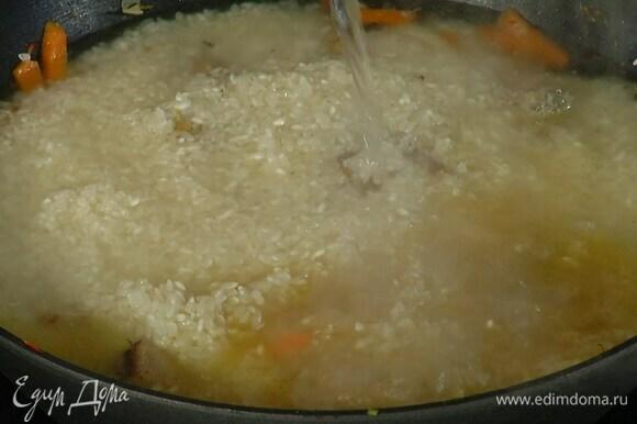 Рис промыть, всыпать в сковороду к мясу и, не перемешивая, равномерно распределить, затем влить кипяток, так чтобы рис был покрыт на 1–2 см.