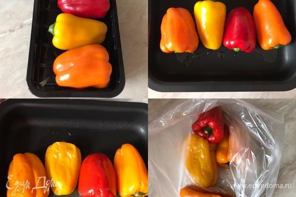 Духовку разогреть до 200°C. Перцы переложить в форму для запекания, сбрызнуть слегка оливковым маслом, закрыть форму фольгой и поставить в духовку. Запекать перцы до готовности, примерно 40–50 минут. Готовые горячие перцы переложить в пакет и дать им остыть.