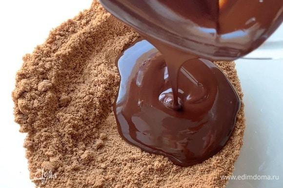 Влейте шоколад к печенью, перемешайте. Дно формы застелите пергаментом и выложите шоколадную основу.