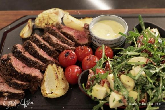 Сервируйте блюдо: на большую тарелку выложите салат, куски мяса и овощи гриль, в отдельной пиале подайте соус. Приятного аппетита!