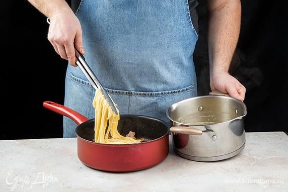В сковороду с беконом добавьте спагетти.